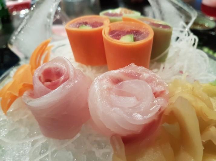 מבחר סשימי בשני סוגים - רול של מבחר דגים נאים קצוצים ועטופים בגזר ובמלפפון והשני, פרחי אוסוזוקורי לצד רוטב פונזו